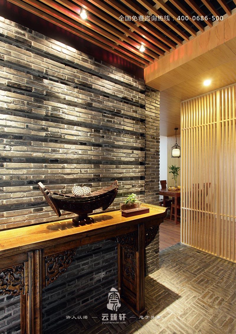 此处的中式玄关装修用青砖作为背景墙,中式木质雕花的桌案,上面
